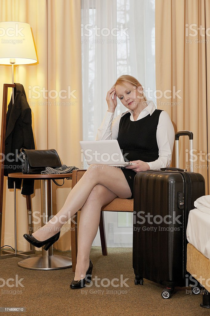 traveling businesswoman using laptop in hotel room stock photo