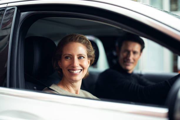 Traveling by a car Handsome adult couple is traveling by a car. They are looking at some point through the window and smiling. georgijevic frankfurt stock pictures, royalty-free photos & images