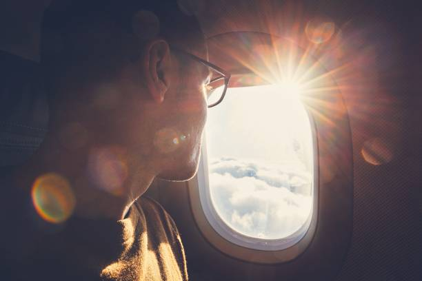 Traveling by airplane Young man looking out through window of the airplane during beautiful sunrise. passenger stock pictures, royalty-free photos & images