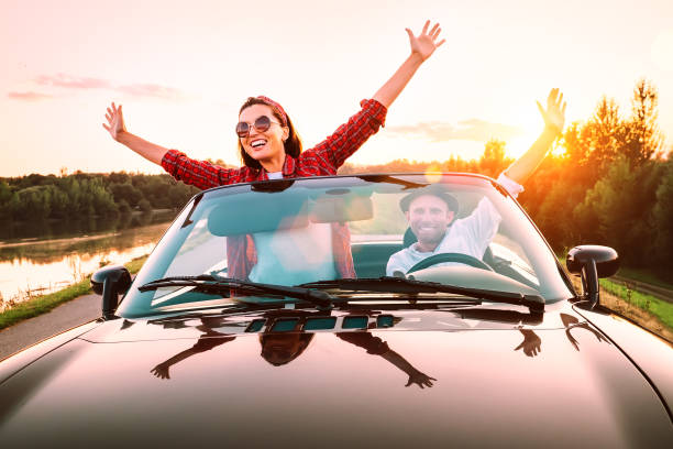 Viajando en coche-feliz pareja en el amor ir por Cabriolet coche en la hora del atardecer - foto de stock