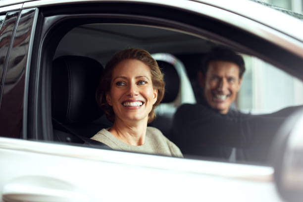 Traveling by car Handsome adult couple is traveling by a car. They are looking through the window and smiling. georgijevic frankfurt stock pictures, royalty-free photos & images