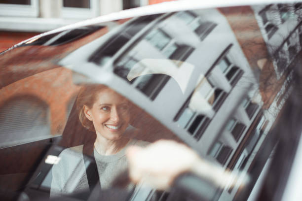 Traveling by car Handsome adult couple is traveling by a car. He is looking at her and smiling. georgijevic frankfurt stock pictures, royalty-free photos & images