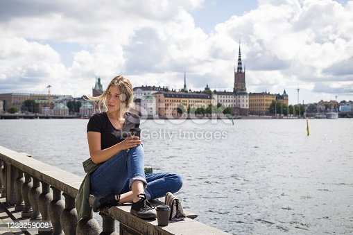 Young woman drinking coffee while relaxing on a stone wall near a river
