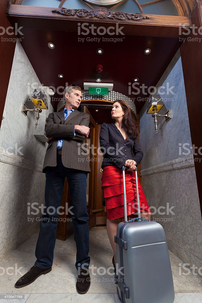 Traveling couple in hotel lobby arguing stock photo