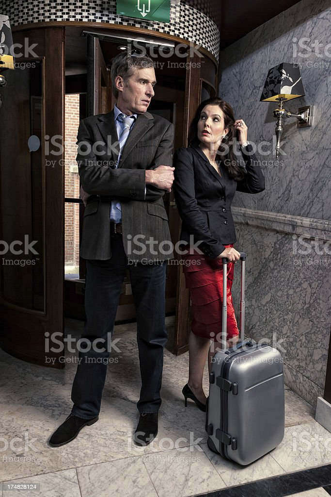 Traveling couple in hotel lobby stock photo