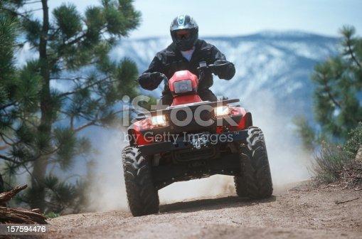 Man riding ATV on dusty mountain trail.