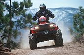 istock ATV traveling down a dust mountain trail. 157594476