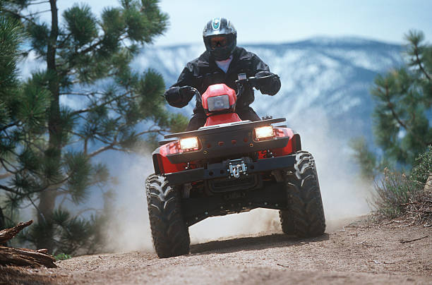 ATV traveling down a dust mountain trail. Man riding ATV on dusty mountain trail. quadbike stock pictures, royalty-free photos & images