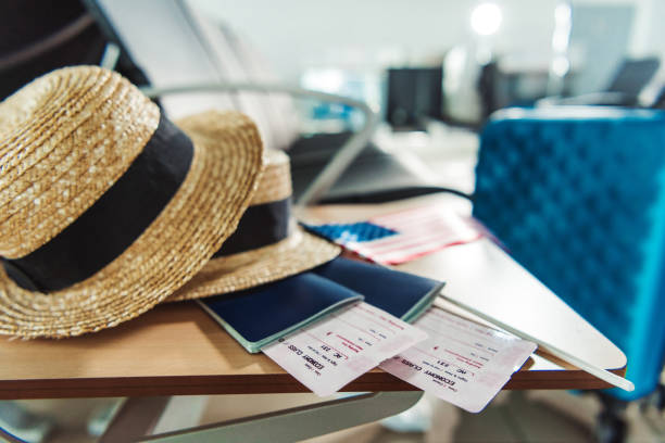 traveling equipment on chair at airport - aeroplane ticket stock photos and pictures