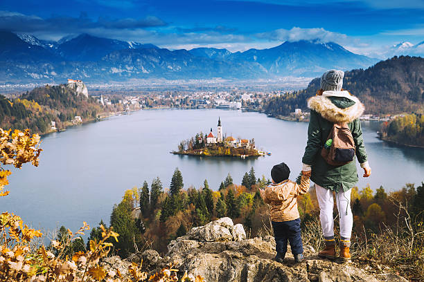 traveling family looking on bled lake, slovenia, europe - europareisen stock-fotos und bilder