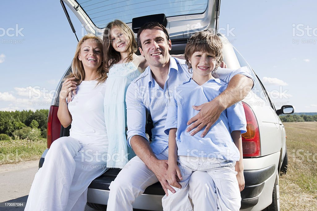 Traveling family sitting on a car trunk in minivan. royalty-free stock photo