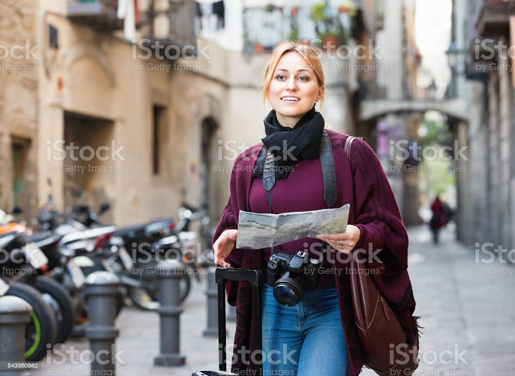 Traveling girl searching for direction using paper map stock photo