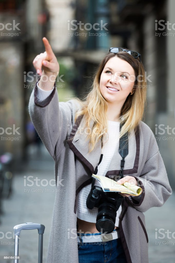traveling girl searching for the direction using a booklet in the town royalty-free stock photo