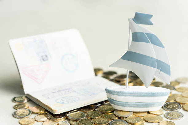 Traveling, holiday, summer and vacation  concept. Mini sailboat and passport on pile of coins. stock photo