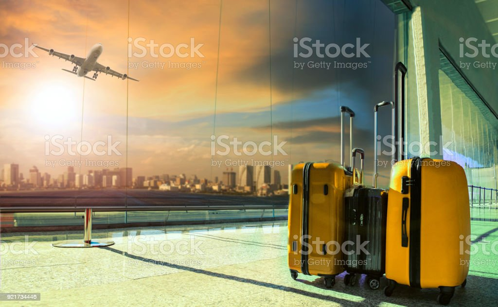 Cтоковое фото traveling luggage in airport terminal building with passenger plane flying over runway