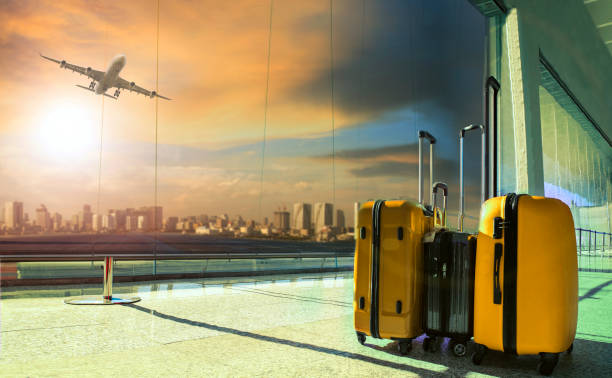 traveling luggage in airport terminal building with passenger plane flying over runway stock photo