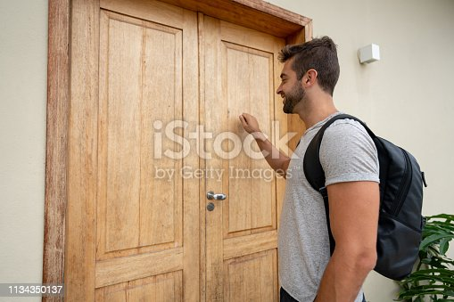 Portrait of a happy traveling man knocking on the door of a lodging house where he's staying – lifestyle concepts