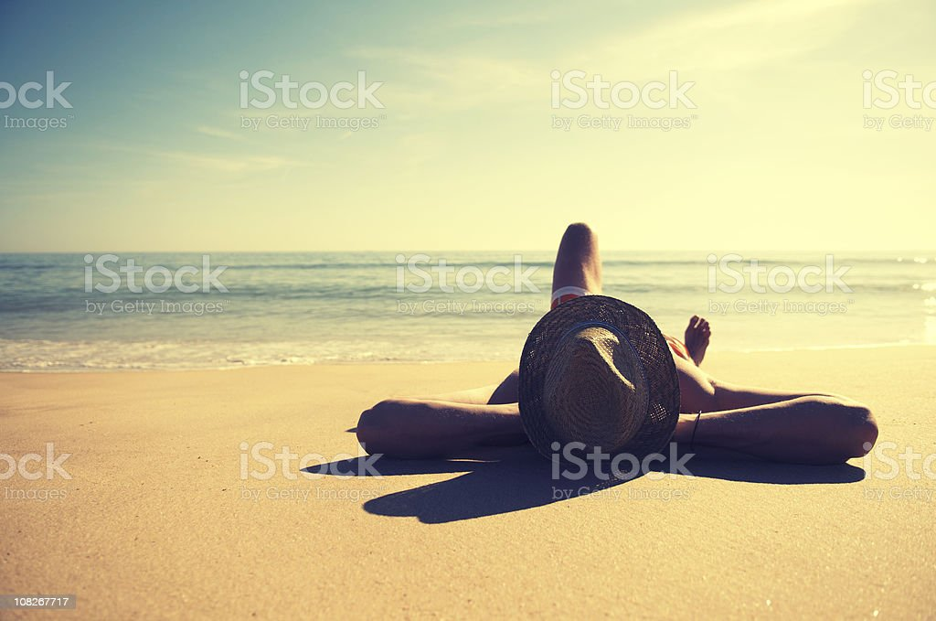 Traveling Man Relaxing on Tranquil Vintage Beach Wearing Hat stock photo