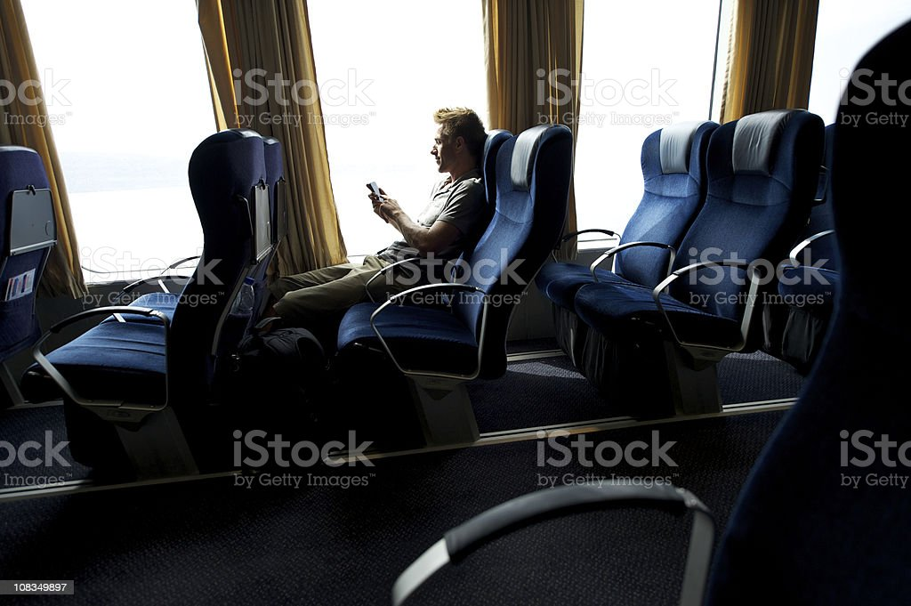 Traveling Man Using Smartphone Texting in Window Seat stock photo