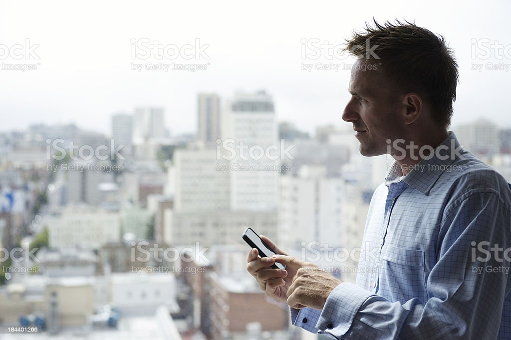 Traveling Man Using Smartphone Thinking in front of City Skyline stock photo