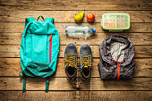 Traveling - packing (preparing) for adventure school trip concept. Backpack, boots, jacket, lunch box, water and fruits on wooden background captured from above (flat lay).