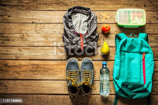 Traveling - packing (preparing) for adventure school trip concept. Backpack, boots, jacket, lunch box, water and fruits on wooden background captured from above (flat lay). Free text (copy) space.