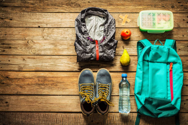 Traveling - packing (preparing) for adventure trip concept Traveling - packing (preparing) for adventure school trip concept. Backpack, boots, jacket, lunch box, water and fruits on wooden background captured from above (flat lay). Free text (copy) space. field trip stock pictures, royalty-free photos & images