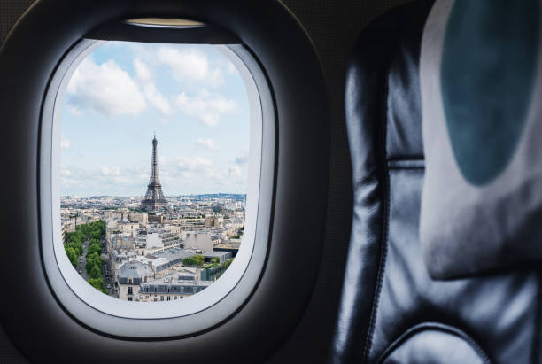 Traveling Paris, France famous landmark and travel destination in Europe. Aerial view Eiffel Tower through airplane window stock photo