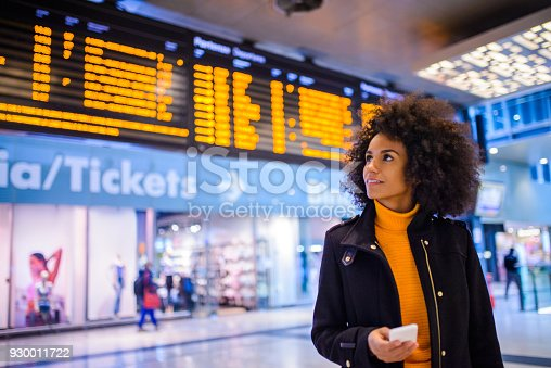 Smiling woman using mobile phone at the airport.