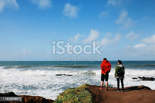 Two people traveling around the California coastline beach in San Mateo county, near Santa Cruz. They're wearing hooded jackets on a windy day as the waves crushing against the shore in this surfer's paradise.
