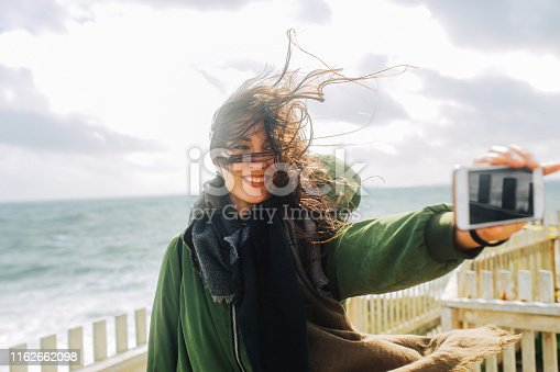 Young woman traveling around the California coastline beach in San Mateo county, near Santa Cruz. She is wearing a hooded jacket on a windy day as the waves crushing against the shore in this surfer's paradise.