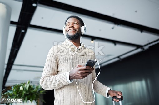 Happy young casual traveler with smartphone and headphones listening to his favorite music in airport lounge