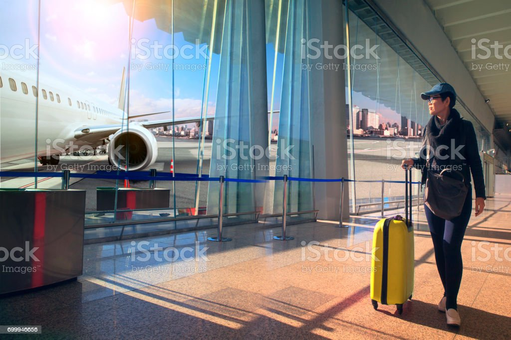 traveling woman and luggage walking in airport terminal and air plane flying outside stock photo
