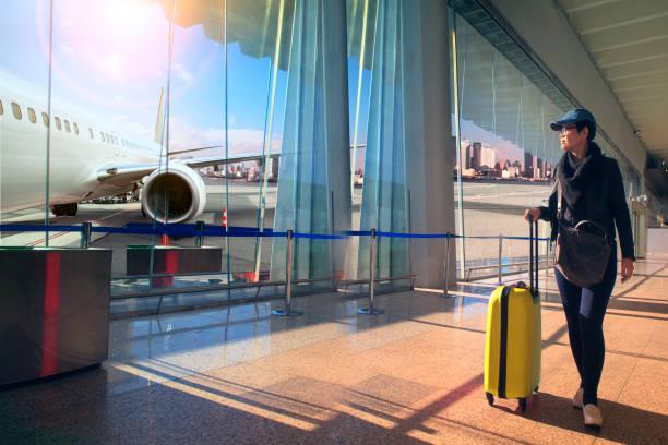 viajando a mulher e a bagagem andando no terminal do aeroporto e avião ar voando lá fora - foto de acervo