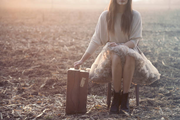 traveling woman sits down to rest after a long trip - donna valigia solitudine foto e immagini stock