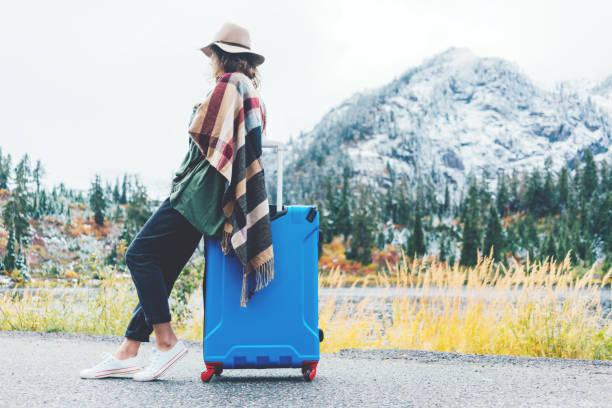 frau sitzt auf ihrem blauen koffer neben wilde landschaft reisen - hippie kleider stock-fotos und bilder