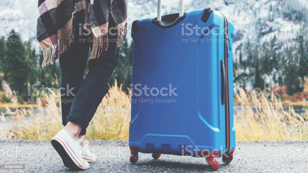 Frau stand in der Nähe ihrer blauen Koffer neben wilde Landschaft reisen – Foto