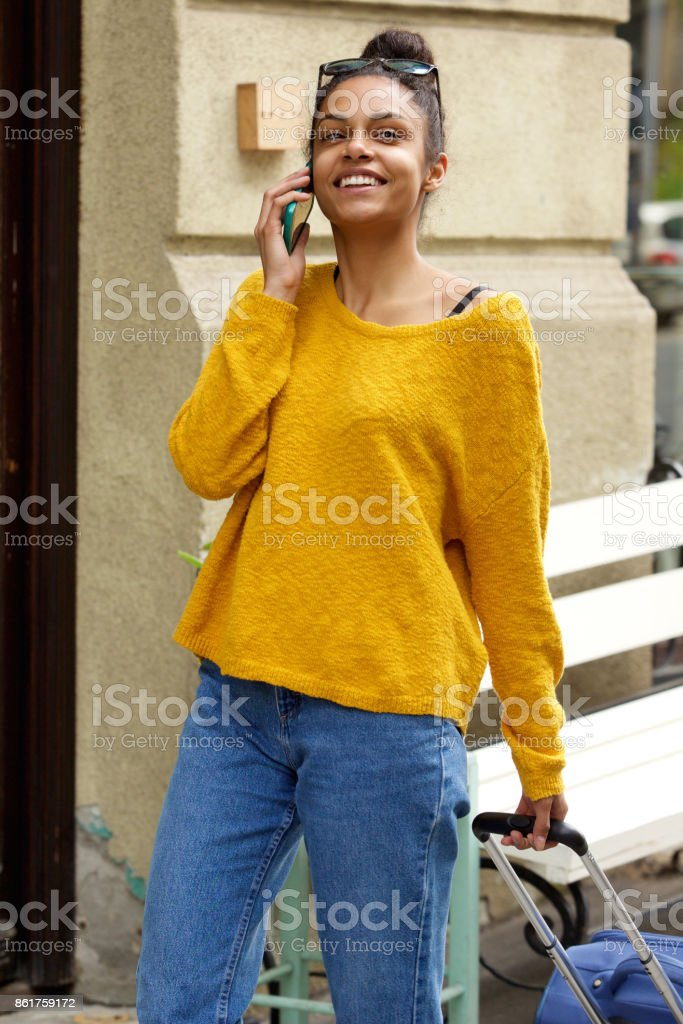 Traveling woman walking and using cell phone stock photo