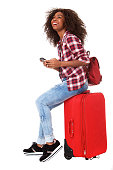 istock Traveling woman with phone sitting on suitcase 992844240