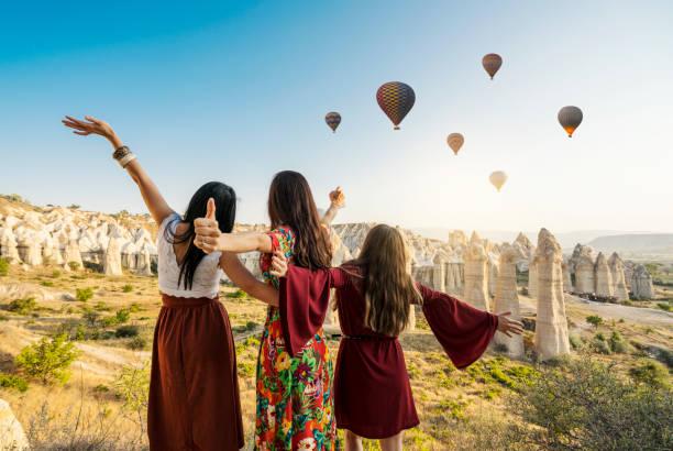 reizen vrouwen kijken naar lucht ballonnen in de lucht in cappadocië vallei. - aardpiramide stockfoto's en -beelden