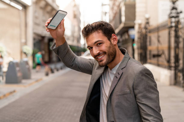 le jeune homme de voyage commande un taxi avec son téléphone - homme faire coucou voiture photos et images de collection