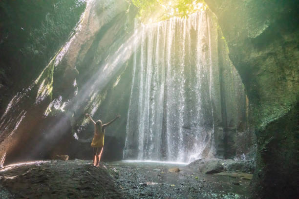 Traveling young woman arms outstretched in tropical rainforest in Bali embracing the beauty in nature. People travel nature concept. Traveling young woman arms outstretched in tropical rainforest in Bali embracing the beauty in nature. People travel nature concept. sun shining through dresses stock pictures, royalty-free photos & images