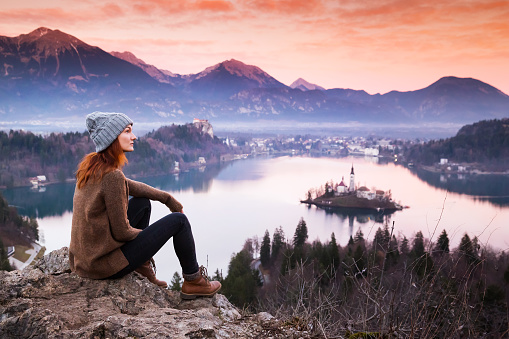 629376126 istock photo Traveling young woman looking on sunset on Bled Lake, Slovenia. 629376018