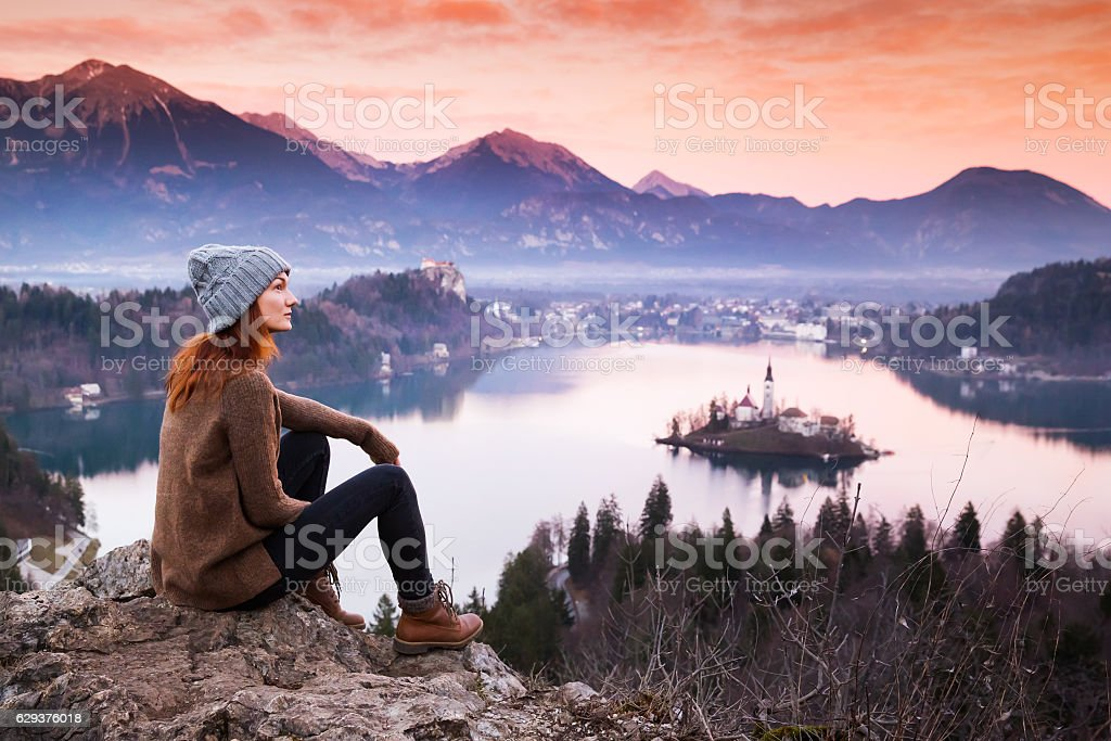 Traveling young woman looking on sunset on Bled Lake, Slovenia. stock photo