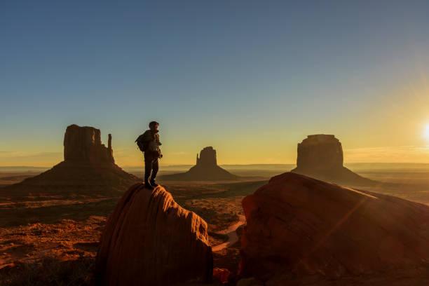 een reiziger bewonderen zonsopgang in monument valley, arizona - natuurreservaat stockfoto's en -beelden