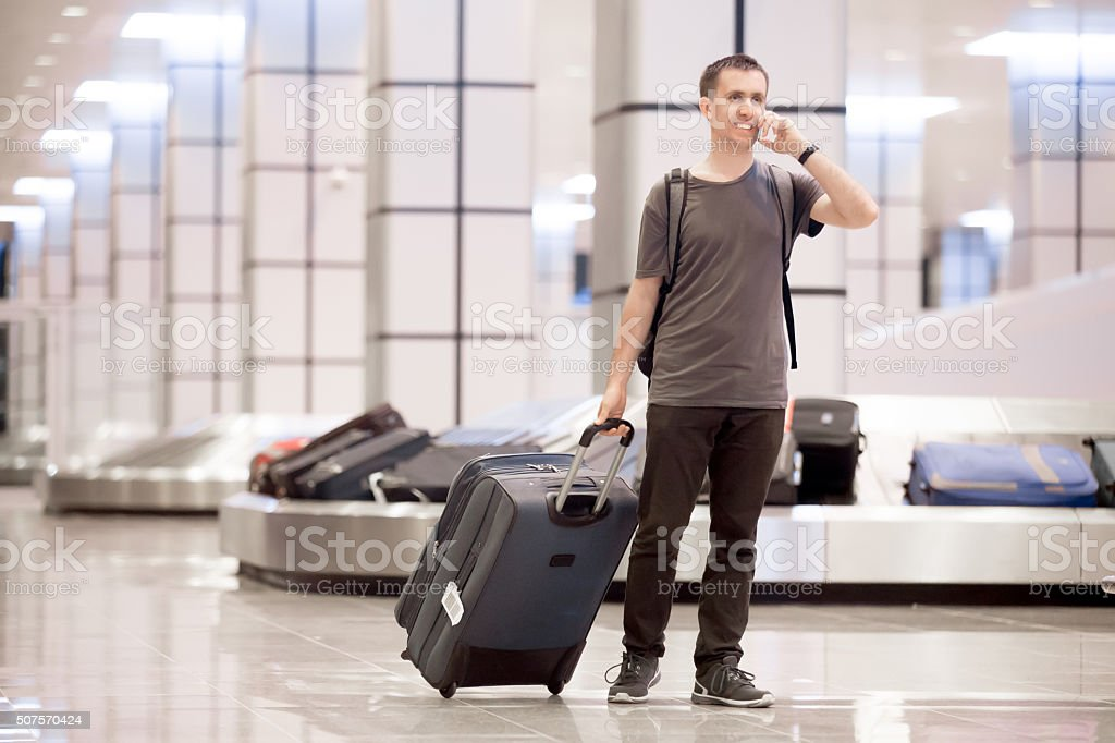 Traveller at conveyor belt on phone stock photo