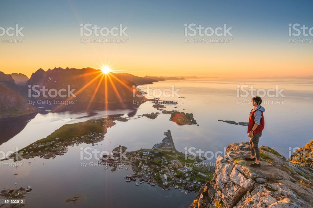 Traveller enjoy summer view of Lofoten Islands in Norway with sunset scenic stock photo