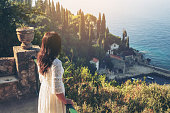Woman traveller enjoys scenic view of Adriatic coast in Trsteno, Dalmatia, Croatia. Tourist attraction near Dubrovnik old town.