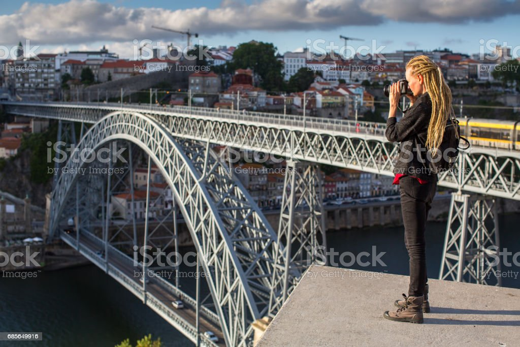 Traveller girl photographer with blonde dreadlocks is takes photo Dom Luis I bridge over Douro river, Porto, Portugal. royalty-free 스톡 사진