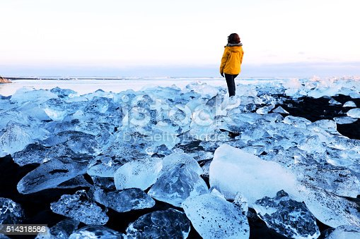 A female traveller is standing in the surreal ice landscape on the beach near Jokulsarlon glacial lagoon in Iceland. Many big pieces of ice are washed ashore. The icebergs are coming from a melting Vatnajokull Glacier and are scattered all along the coast. This image is taken on a cold winter evening.